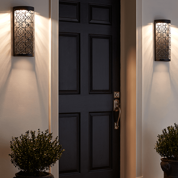 Dramatic scroll work sconces on each side of an entry door.  Lighting has intregal LED lights.