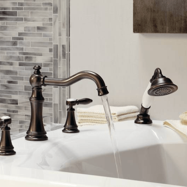 Weymouth by Moen tub faucet with hand shower features and old world design with warm Oil Rubbed Bronze finish and white accents